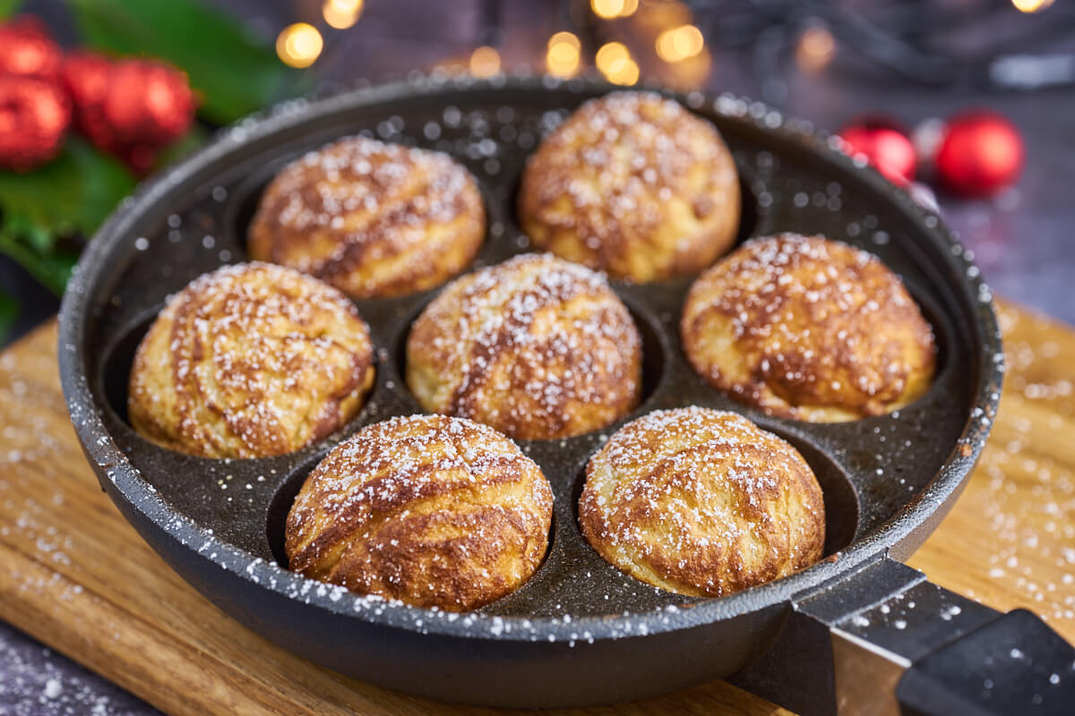 Homemade aebleskiver in an aebleskiver pan with icing sugar and Christmas decorations in the background
