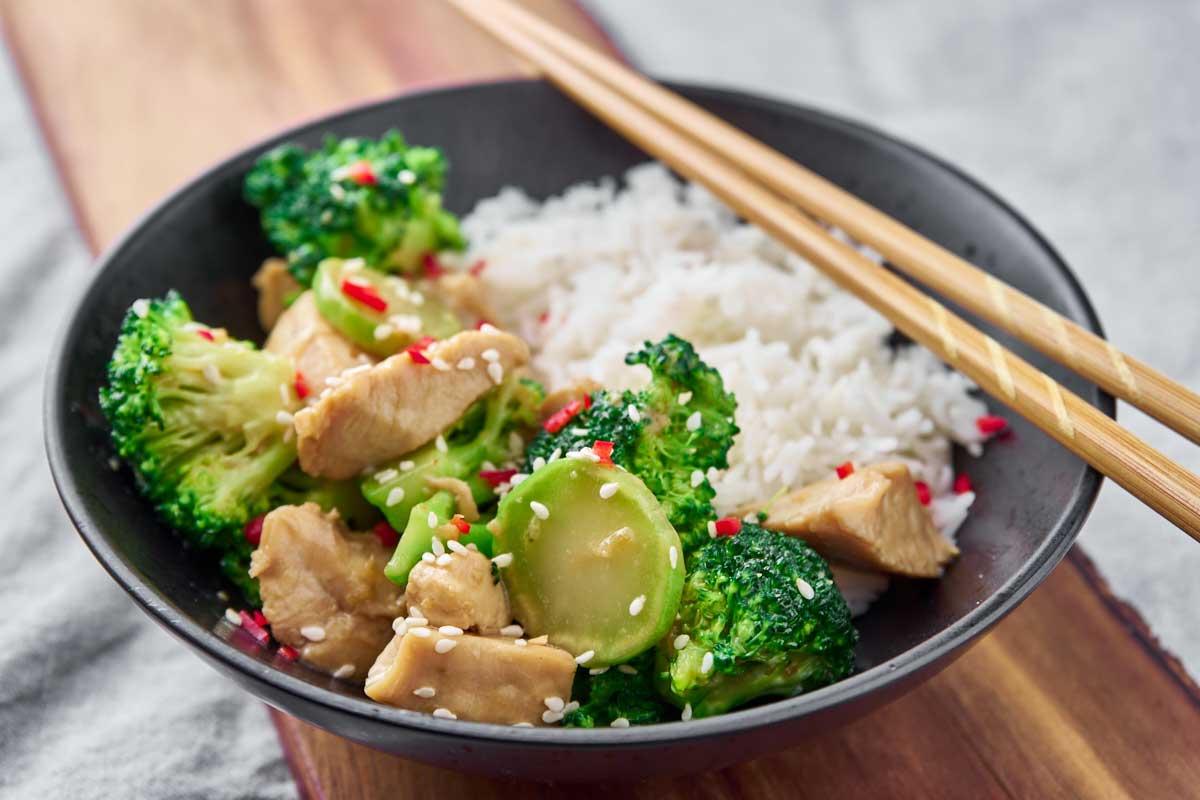 Wokret med kylling og broccoli serveret i skål med ris til og drysset med chili og sesam