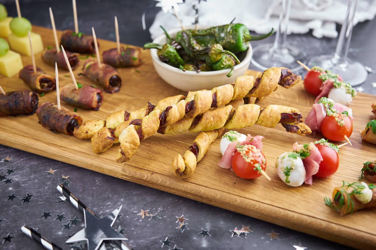 tapasbræt med snacks til nytårstalen, pindemadder med ost, dadler med bacon, butterdejsstænger, tapas peber, mozzarellaspyd med tomat og skinke og muslinger med bacon og estragonmayonnaise