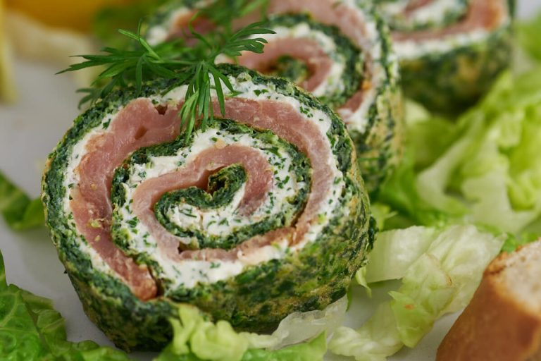 Spinach roulade with smoked salmon and cream cheese filling served with dill, lemon, lettuce and bread