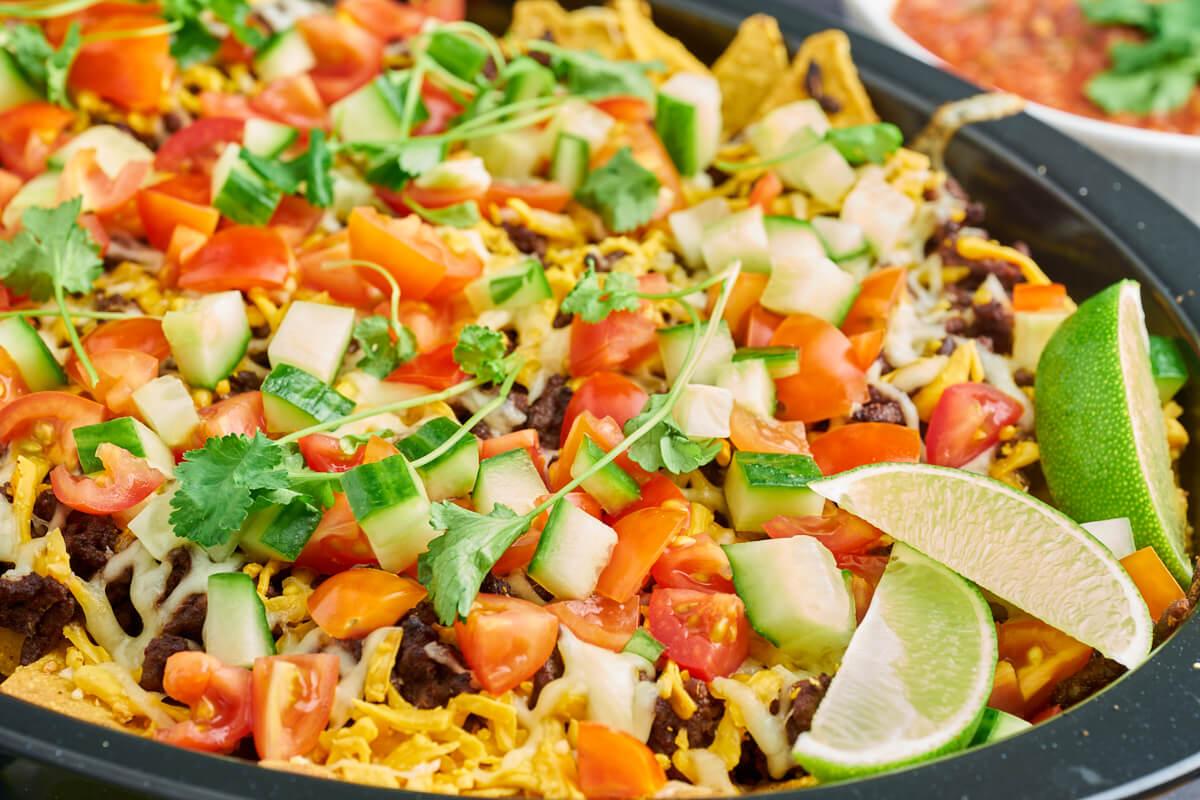 Nachos deluxe med hakket oksekød, mozzarella, cheddar, tomat og agurk på toppen