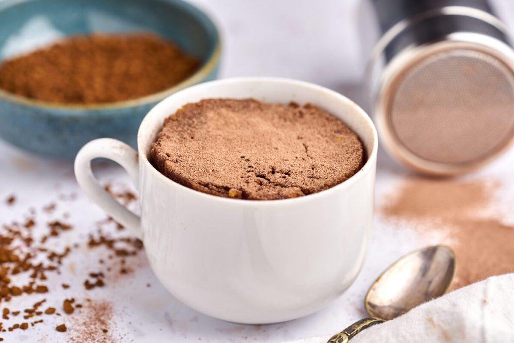 Cafe latte kage i kop bagt i mikroovn med instant kaffe og kakaopulver bagved