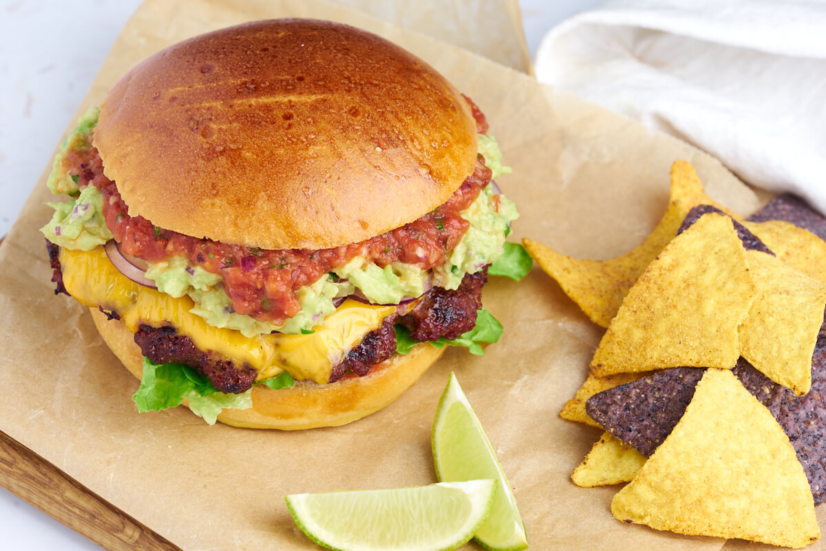 homemade Mexican burger with guacamole, salsa and cheddar as well as tortilla chips