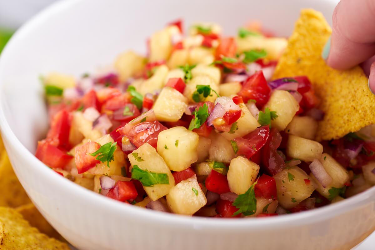 hvid skål med ananassalsa og nachos chip der bliver dyppet i salsaen