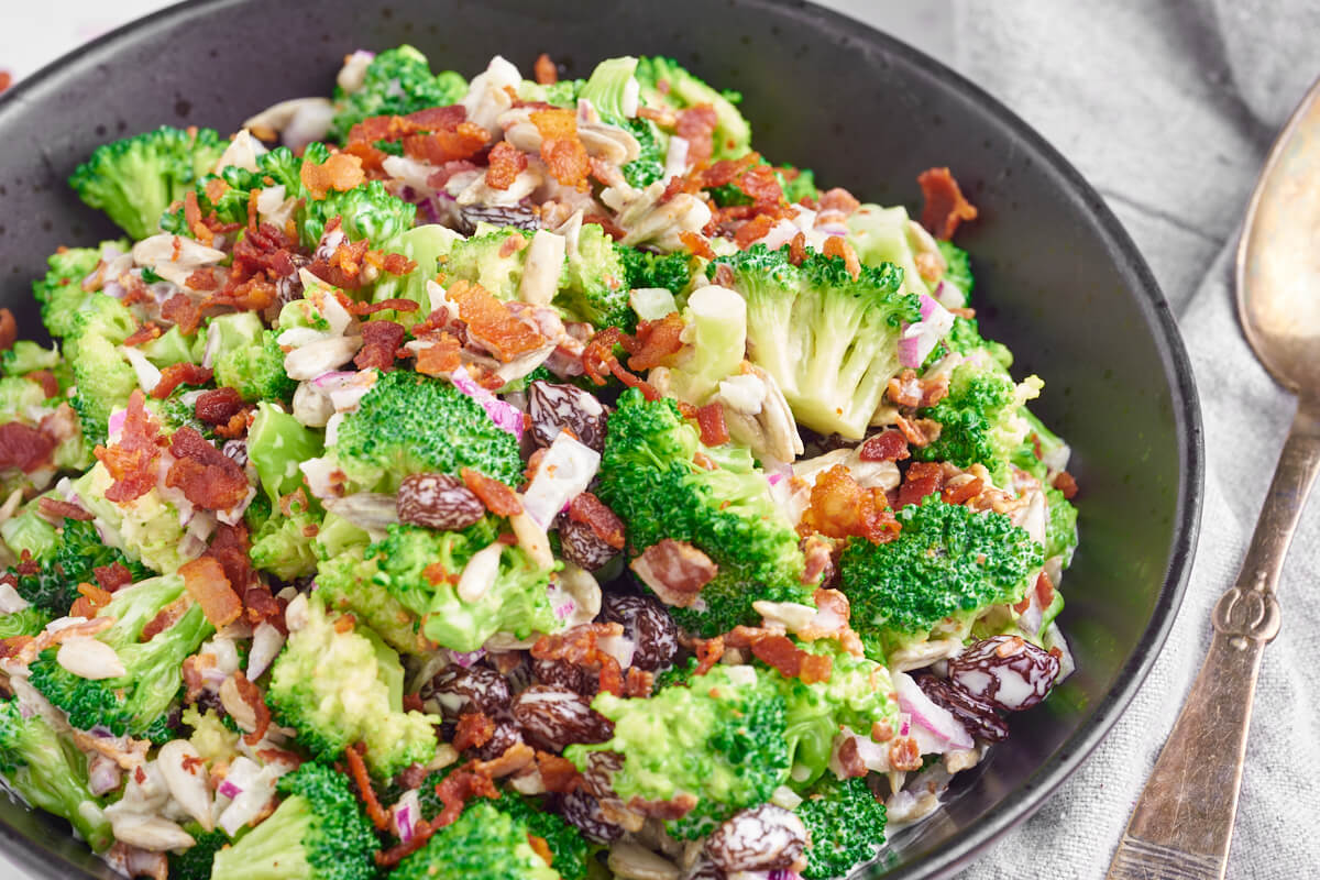 sort skål med broccolisalat med bacon, rødløg og rosiner